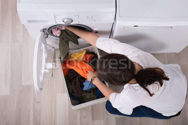 Stock photo: Elevated View Of A Woman Loading Clothes In Washing Machine