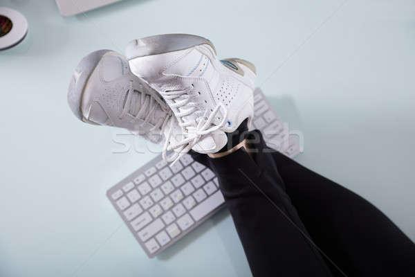 Businesswoman's Crossed Leg On Computer Keyboard Stock photo © AndreyPopov