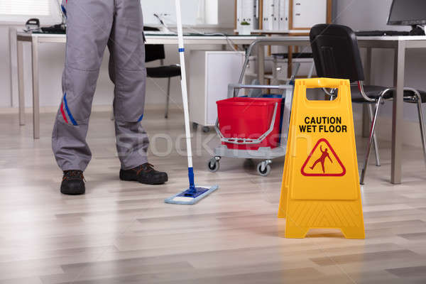 Cleaner Standing With Mop And Caution Wet Floor Sign Stock photo © AndreyPopov