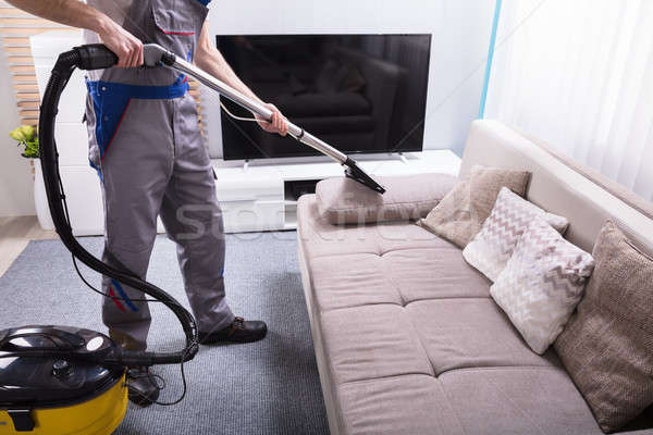 Person Cleaning Sofa With Vacuum Cleaner Stock Photo C Andriy Popov