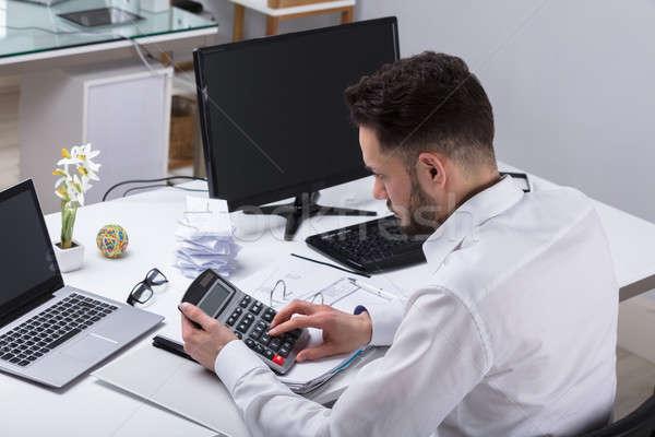 Fiatal üzletember számla számológép munkahely férfi Stock fotó © AndreyPopov