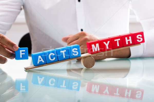 Businessman showing unbalance between facts and myths Stock photo © AndreyPopov