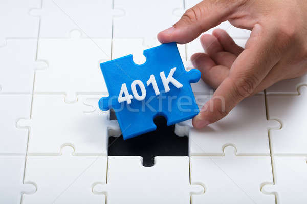 Man placing final 401k piece into jigsaw puzzle Stock photo © AndreyPopov