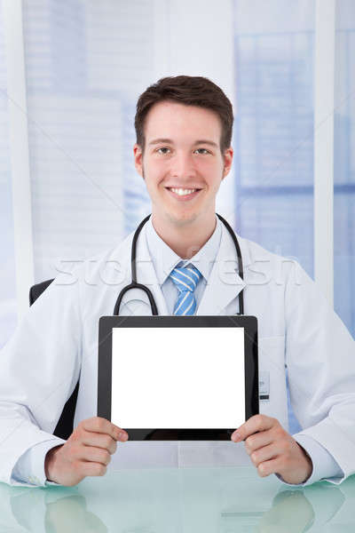 Stock photo: Confident Doctor Displaying Digital Tablet At Desk