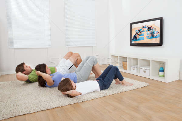 Family Doing Situps While Watching TV Stock photo © AndreyPopov