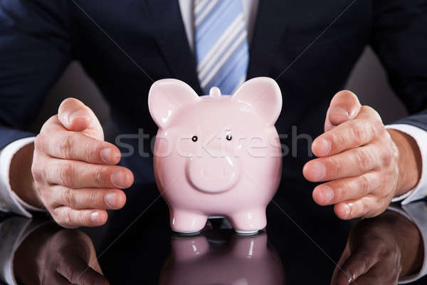 Businessman Protecting Piggybank With Cupped Hands On Desk Stock photo © AndreyPopov