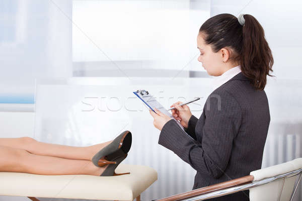 Psychiatrist Writing On Clipboard Stock photo © AndreyPopov