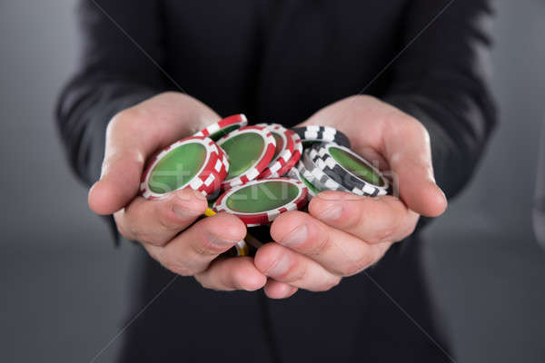 Businessman Holding Poker Chips In Cupped Hands Stock photo © AndreyPopov