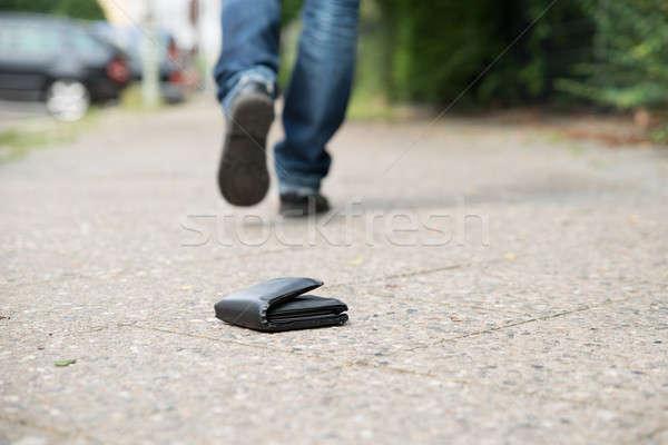 Man Walking Against Fallen Wallet On Street Stock photo © AndreyPopov