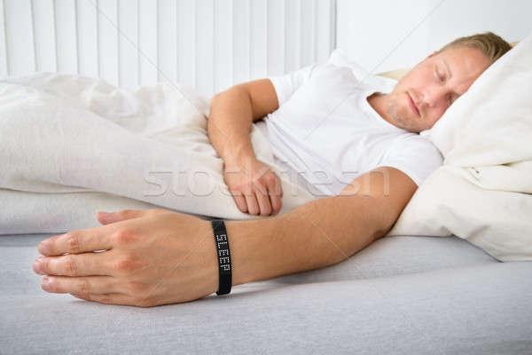 Fiatalember alszik visel okos karszalag portré Stock fotó © AndreyPopov