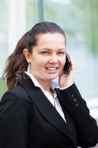 Confident Businesswoman Answering Cellphone Outdoors Stock photo © AndreyPopov