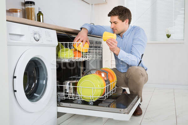 Man Arranging Dishes In Dishwasher Stock photo © AndreyPopov