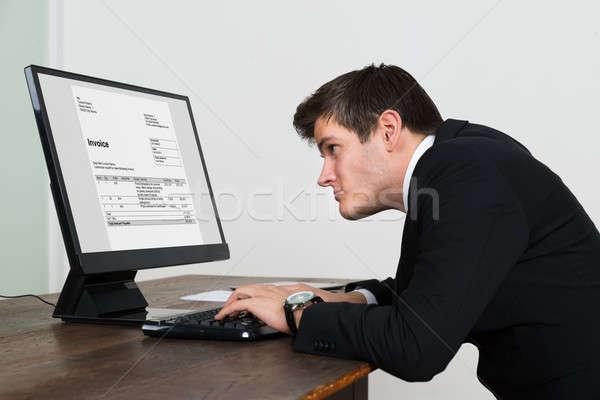 Imprenditore guardando fattura computer giovani schermo del computer Foto d'archivio © AndreyPopov