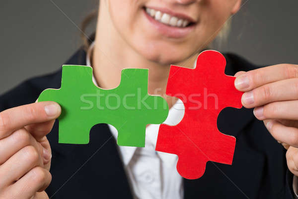 Midsection Of Businesswoman Solving Jigsaw Puzzle Stock photo © AndreyPopov