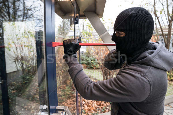 Man Using Crowbar To Open Glass Door Stock photo © AndreyPopov