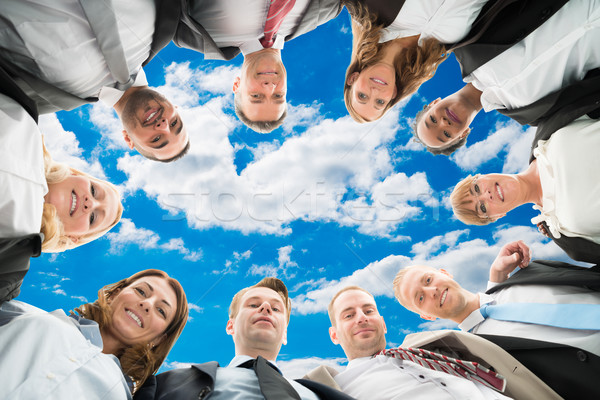 Diverse Business People Forming Huddle Against Sky Stock photo © AndreyPopov