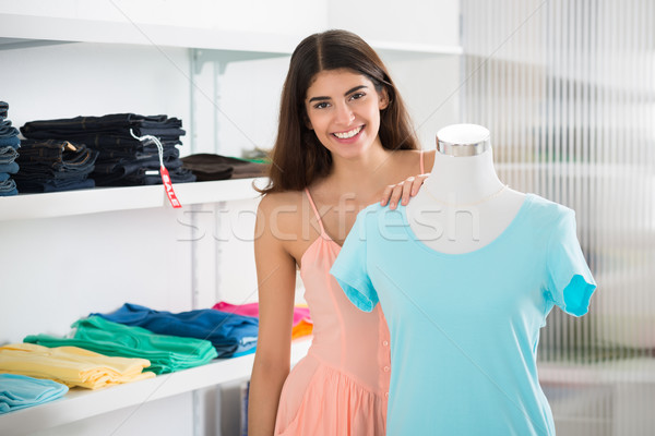 Stock photo: Smiling Woman Standing By Mannequin Displaying Top In Store