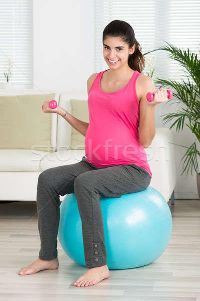 Boldog terhes nő emel súlyzók portré ül Stock fotó © AndreyPopov