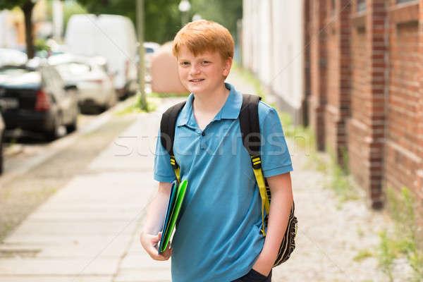 Glimlachend schooljongen permanente trottoir portret map Stockfoto © AndreyPopov