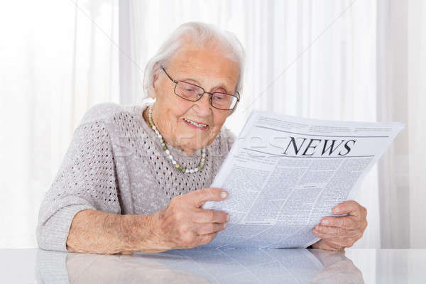 Senior mulher leitura jornal feliz secretária Foto stock © AndreyPopov