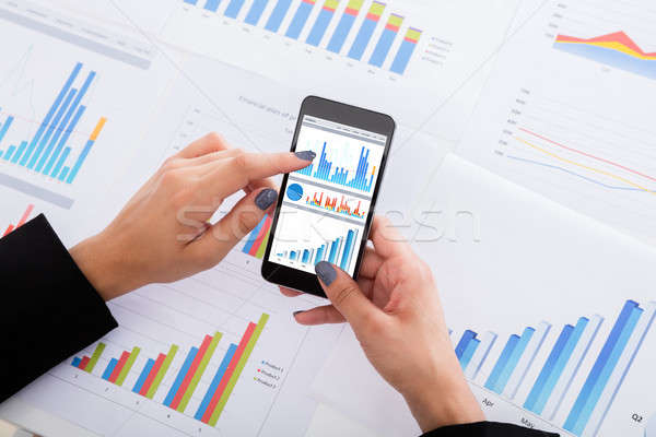 Businesswoman Analyzing Financial Graphs Using Smartphone Stock photo © AndreyPopov