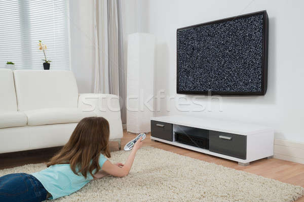 Girl With Remote Control Watching Television Stock photo © AndreyPopov