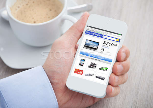 Person Hand Shopping Online While Holding Mobilephone Stock photo © AndreyPopov