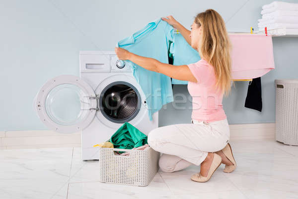 Stock photo: Woman Looking At Blue T-shirt In Utility Room