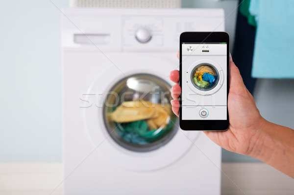 Persoon wasmachine mobieltje hand smart Stockfoto © AndreyPopov