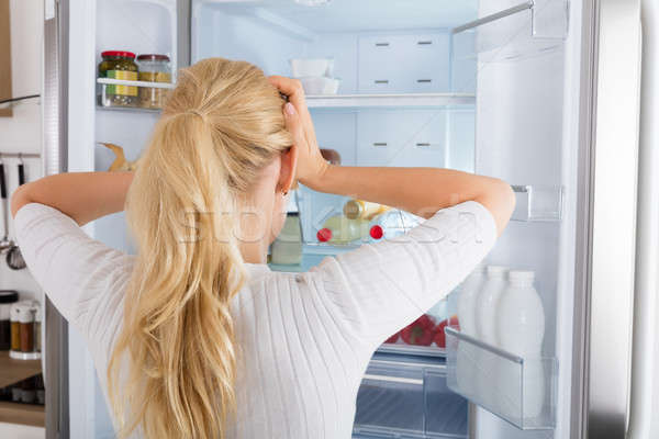 Woman Looking Inside The Fridge Stock photo © AndreyPopov