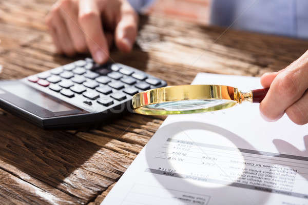 Accountant Using Magnifying Glass While Calculating Finance Stock photo © AndreyPopov