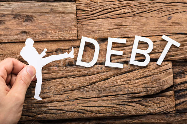 Paper Cut Out Figure Kicking The Debt Word Stock photo © AndreyPopov