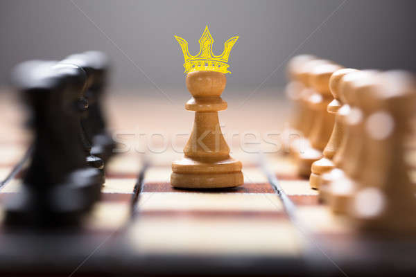Pawn With King Crown Amidst Chess Pieces Stock photo © AndreyPopov