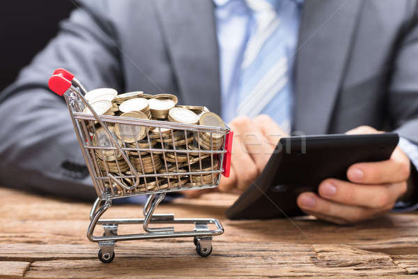 Businessman Using Calculator By Shopping Cart Filled With Coins Stock photo © AndreyPopov