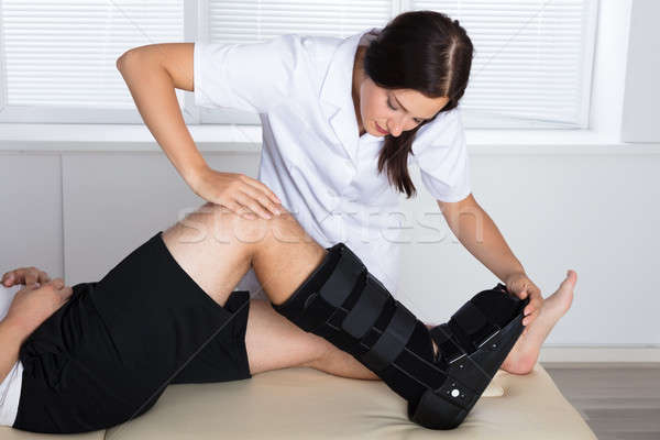 Orthopedist Adjusting Walking Brace On Patient's Leg Stock photo © AndreyPopov