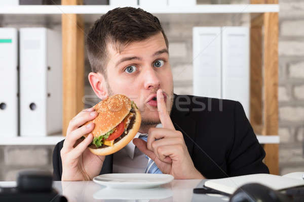 Hungry Young Businessman Holding Burger With Finger On Lips Stock photo © AndreyPopov