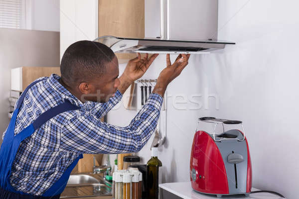 African Male Fixing Kitchen Extractor Filter Stock photo © AndreyPopov
