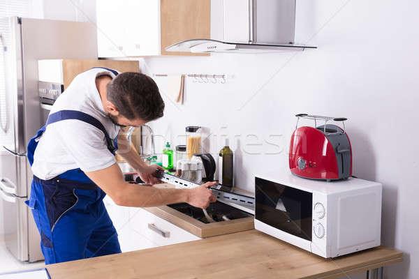 Villanyszerelő javít tűzhely fiatal férfi konyha Stock fotó © AndreyPopov