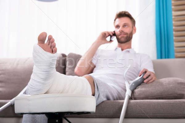 счастливым молодым человеком сломанной ногой говорить смартфон сидят Сток-фото © AndreyPopov
