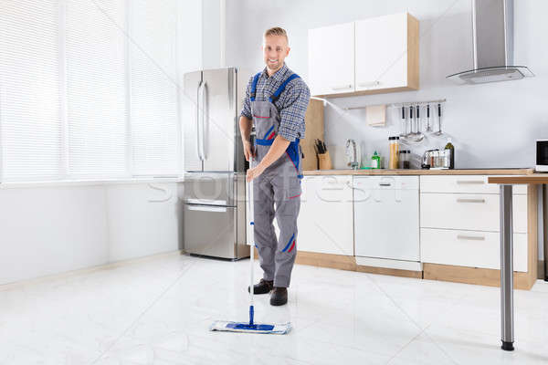 Young Male Worker Mopping Floor Stock photo © AndreyPopov