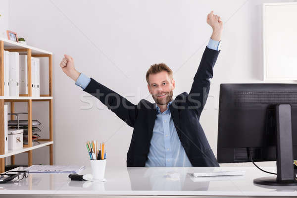 Happy Young Businessman Sitting In Office Stock photo © AndreyPopov