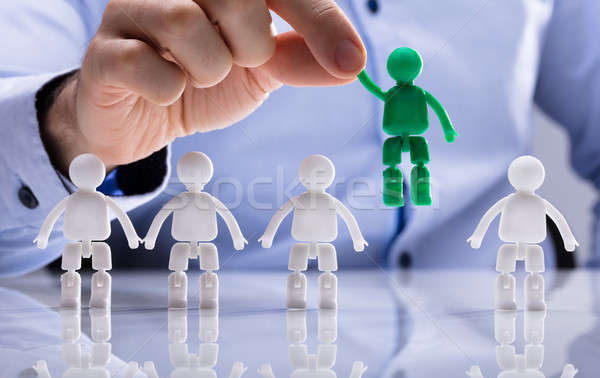 Person Selecting Green Figure Amongst White Human Figures Stock photo © AndreyPopov