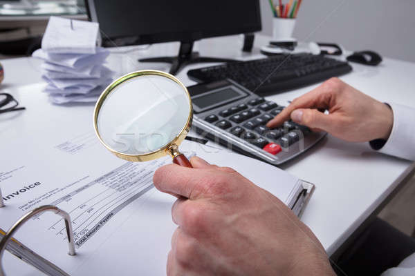 Businessperson Examining Invoice Through Magnifying Glass Stock photo © AndreyPopov