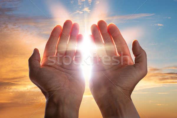 Primo piano pregando mani luce del sole uomo culto Foto d'archivio © AndreyPopov