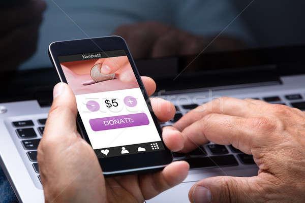 Adam cep telefonu bağış uygulaması ekran Stok fotoğraf © AndreyPopov