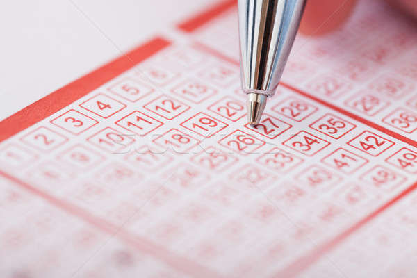 Stock photo: Person Holding Pen Over Lottery Ticket