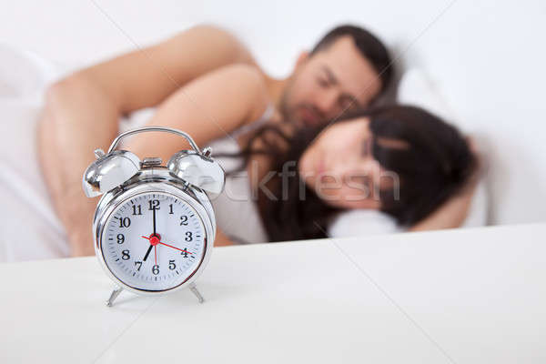 Lovely young couple and alarm clock Stock photo © AndreyPopov