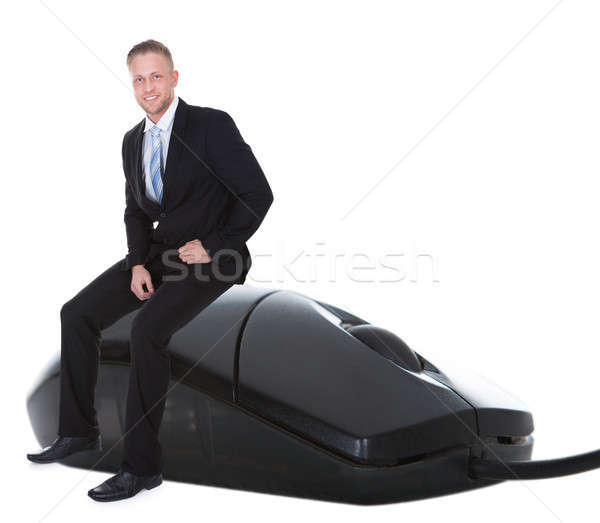 Businessman in a suit sitting on a wired computer mouse Stock photo © AndreyPopov