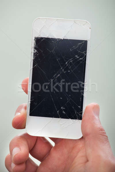 Businessman holding a damaged smartphone Stock photo © AndreyPopov