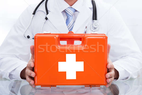 Smiling doctor or paramedic with a first aid kit Stock photo © AndreyPopov
